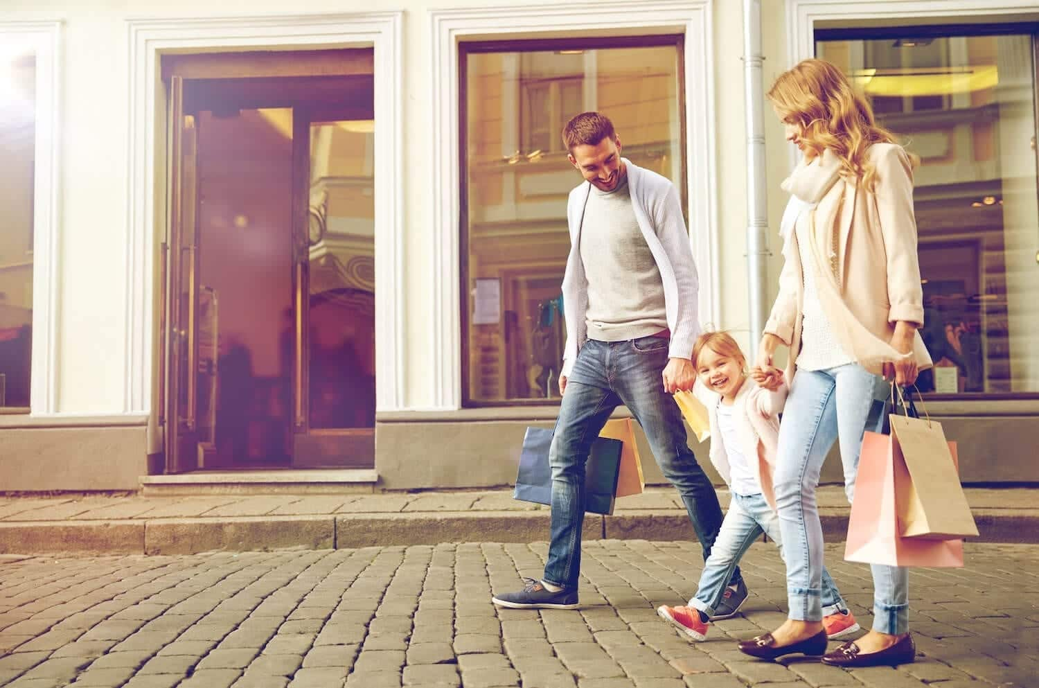 Young family walking with their daughter holding shopping bags