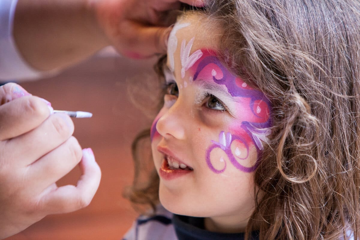 Portrait of little girl getting her faced painted