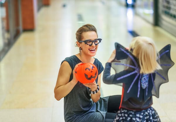 Woman showing a pumpkin toy to a little girl during Halloween