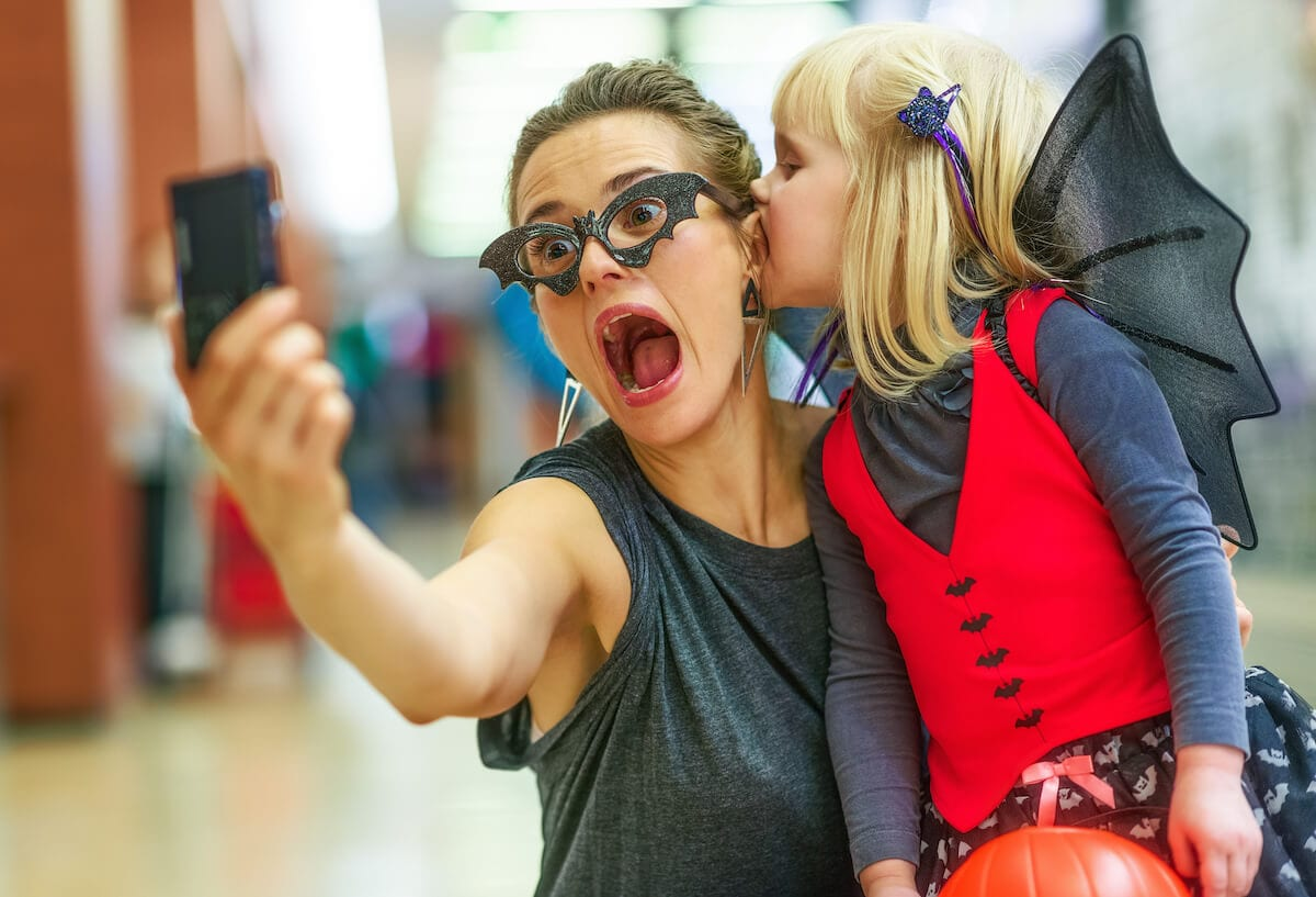 Woman getting a selfie with her kid on Halloween