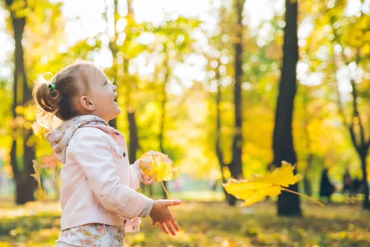 Photo of girl playing with tree leaves