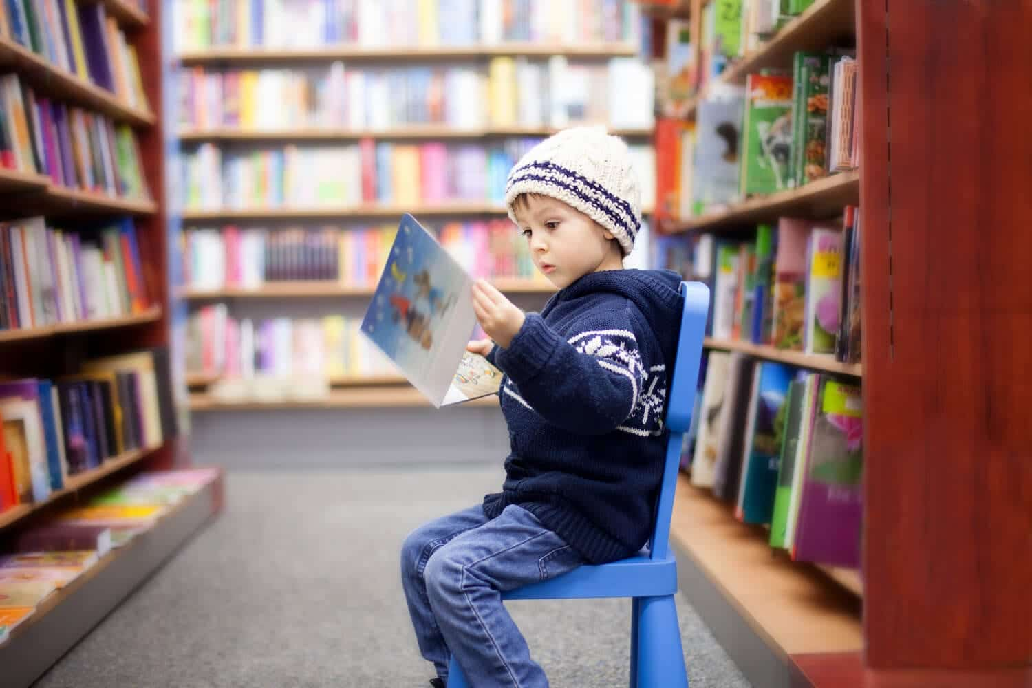 Portrait of kid reading a book in a library