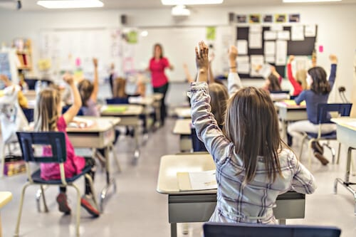 Image of children raising hands up in a classroom